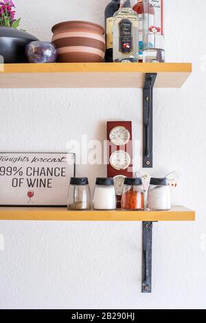 Budapest, Hungary - December 14, 2019: Open storage shelves on the wall with spices and decoration in a bright modern home. - Stock Photo