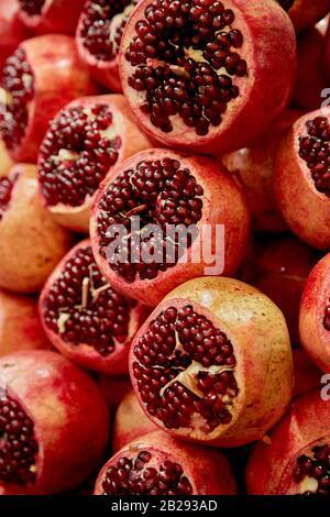 Stacked and Cut Pomegranates at Market Stock Photo