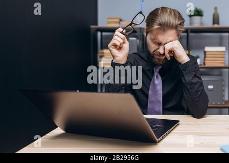 Overworked bearded man in formal clothing sitting at office with laptop and rubbing his eyes. Tired mature manager taking off eyegasses after long wor - Stock Photo