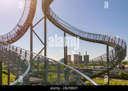 'Tiger and Turtle' or ' Magic Mountain' famous sculpture on top of the hill in Anger park surrounded with  lower industrial landscape and park. Stock Photo