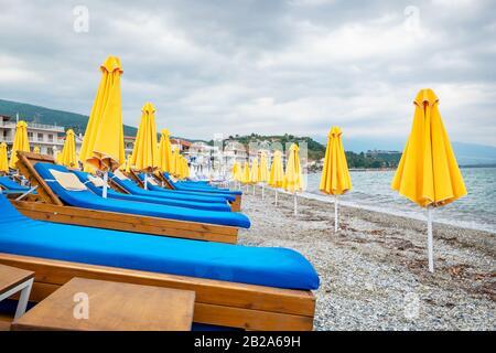 Yellow umbrellas and empty lounge chairs on a pebble beach. Platamonas, Pieria, Greece - Stock Photo