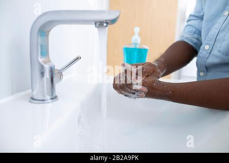 Close Up Of Boy Washing Hands With Soap At Home To Prevent Infection