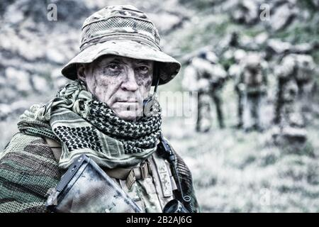 Close-up portrait of brutal commando veteran, experienced army commander or officer with dirty face, wearing camouflage bonnie, shemagh, tactical - Stock Photo