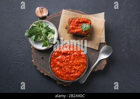 Tasty ajvar on toast. Vegetable sauce or caviar of baked red bell pepper on black. Balkan cuisine. Horizontal orientation. Top view.