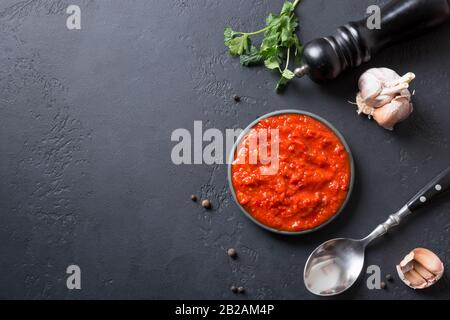 Tasty ajvar on toast. Vegetable sauce or caviar of baked red bell pepper on black. Balkan cuisine. Space for text. Top view.