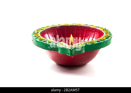Single Clay diya lamp lit during diwali festival. Happy Diwali Greetings Card Design, Indian Hindu Festival of Lights called Diwali. - Stock Photo