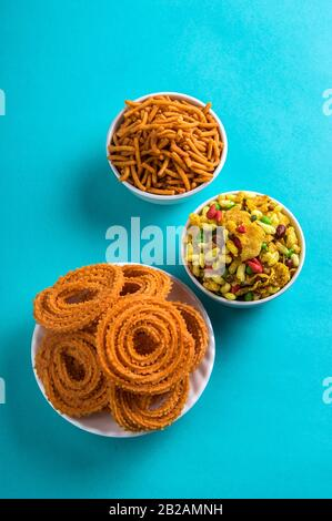 Indian Snack : Chakli, chakali or Murukku and Besan (Gram flour) Sev and chivada or chiwada on blue background. Diwali Food. - Stock Photo