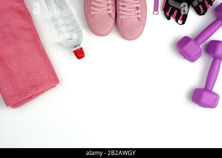 pair of pink leather sneakers, plastic dumbbells and gloves for sports on a white background, sports backdrop, top view, copy space. - Stock Photo