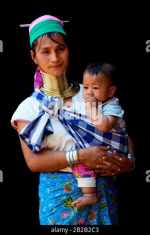 Kayan Lahwi woman carrying her baby and wearing brass neck coils and traditional clothing. The Long Neck Kayan (also called Padaung in Burmese) are a