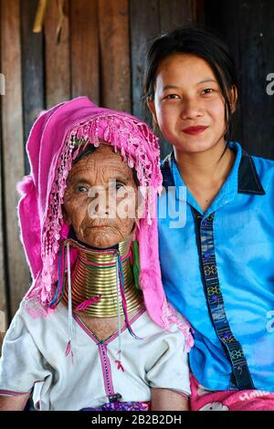 Portrait of an old Kayan Lahwi woman with brass neck coils and traditional clothing with her grand daughter, who does not wear the rings. The Long