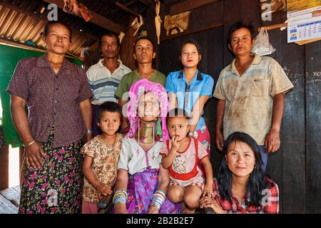 Multi-generational Kayan Lahwi peasant family portrait. The grand mother is wearing the traditional brass neck coils and clothing, which the youger