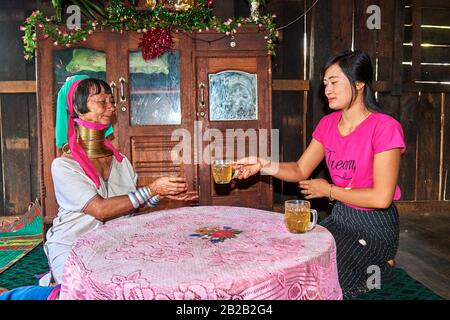Generation gap. Kayan Lahwi woman with brass neck coils and traditional clothing drinking tea with her daughter, who is not wearing any coils and