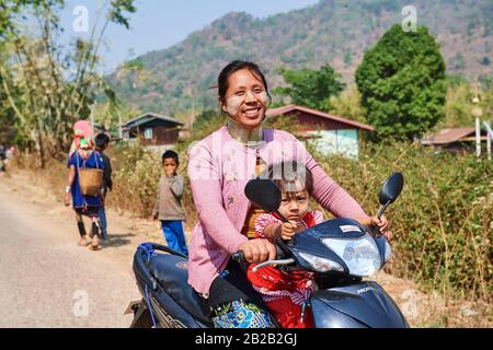Kayan Lahwi woman with brass neck coils and traditional clothing riding a motorbike with her child. The Long Neck Kayan (also called Padaung in - Stock Photo