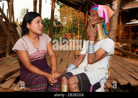 Generation gap. Kayan Lahwi woman with brass neck coils and traditional clothing chatting with her grand daughter, who is not wearing any coils and