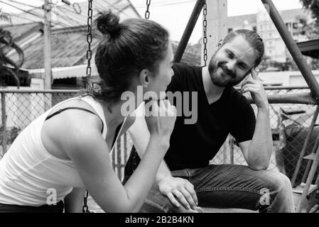 Young happy bearded man looking at young beautiful woman smiling and sitting on metal swings together in love at the old playground - Stock Photo