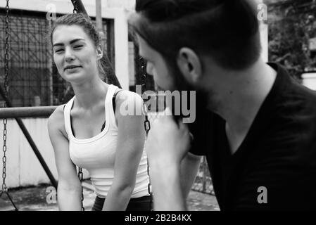 Young happy woman looking at young bearded man smiling and sitting on metal swings together in love at the old playground - Stock Photo