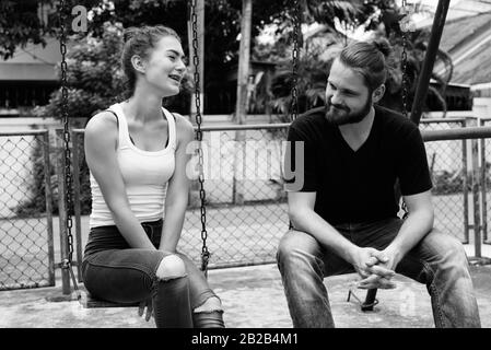 Happy young couple smiling and sitting on the metal swings together in the old playground - Stock Photo