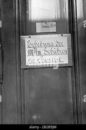 A sign nailed to a door of the passport office in Berlin with the inscription ' Collection of Reichsmark fees for departure '. Citizens have to pay 100 Reichsmark special fees for each trip abroad. - Stock Photo