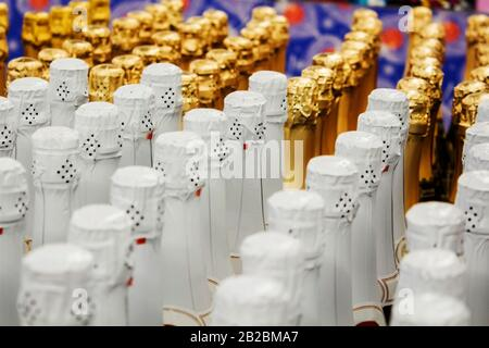 Big amount of golden and white champagne bottles necks and top caps at standing the light background - Stock Photo