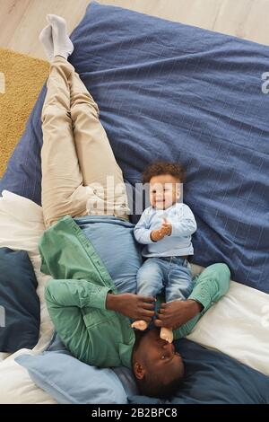 Top view portrait of happy African-American man playing with cute baby son while lying on bed at home, copy space Stock Photo