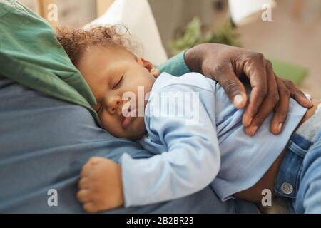 High angle view at cute mixed-race baby sleeping in fathers arms