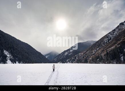 Lonely woman is walking on frozen Kolsai lake with mountains at background in Kazakhstan
