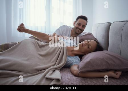 Young couple is lying in bed and waking up in the morning.