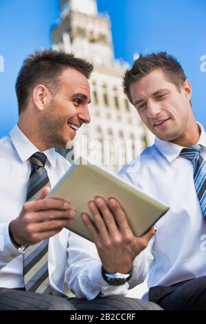 Portrait of handsome businessman showing business plan to the other businessman over digital tablet while sitting