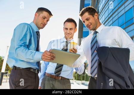 Mature attractive businessman showing and discussing plans over digital tablet with colleagues against office building