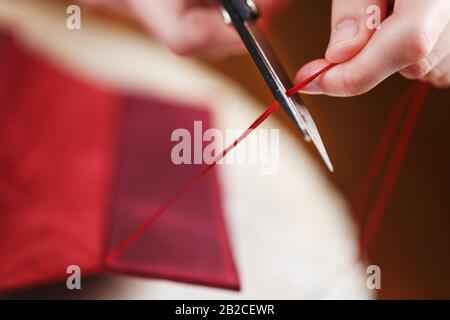 A leather craftsman works with leather. Sews leather goods. Making things handmade. Women's hands with a needle, thread, scissors and a blowtorch. Clo - Stock Photo