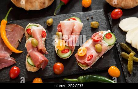 Prosciutto canapes on granite board - top view - Stock Photo