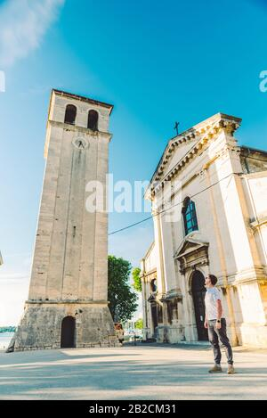 man standing at square looking at old roman cathedral church in pula city - Stock Photo