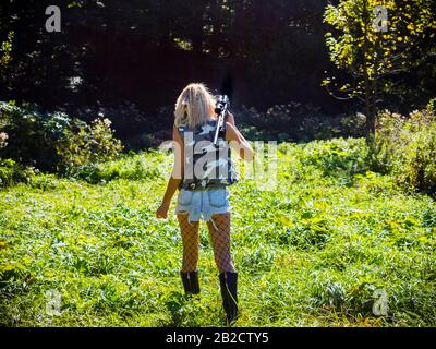 Attractive blonde female aka sharpshooter walking towards dark Green forest hands holding rifle on her shoulder view from back behind rear rearview - Stock Photo