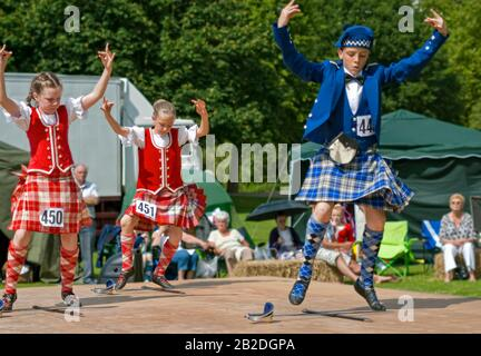 Young Scottish Highland Dancer performing a sword dance during a competition in Colchester, Essex, England - Stock Photo