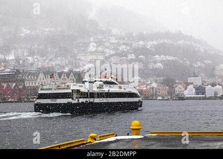 Winter in Bergen, Norway. Snowing heavily. View from the old port of the city, Vaagen. UNESCO Hanseatic architecture at Bryggen. High speed passenger - Stock Photo