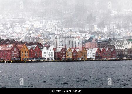 Winter in Bergen, Norway. Snowing heavily. View from the old port of the city, Vaagen. UNESCO Hanseatic architecture at Bryggen. - Stock Photo
