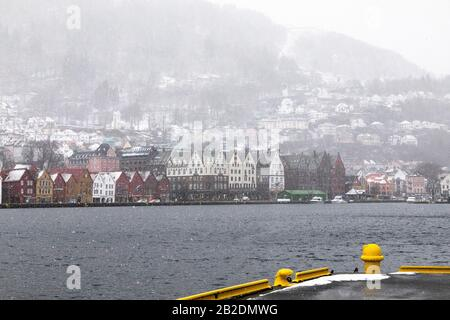 Winter in Bergen, Norway. Snowing heavily. View from the old port of the city, Vaagen. UNESCO Hanseatic architecture at Bryggen. Mount Floeyen (Fløyen - Stock Photo
