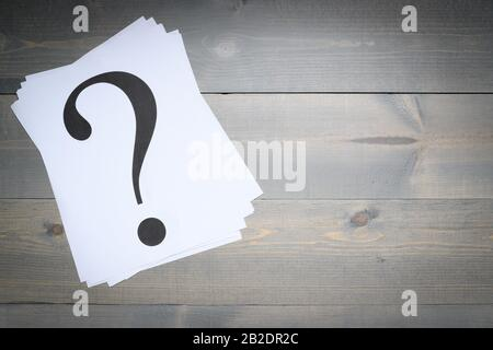 Stack of question marks printed on white paper on a gray board background - Stock Photo