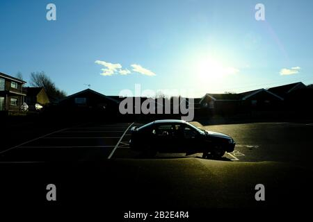 A single car vehicle parked in a disabled parking bay in a large asphalt carpark next to residential bungalows in silhouette late afternoon winter sun - Stock Photo
