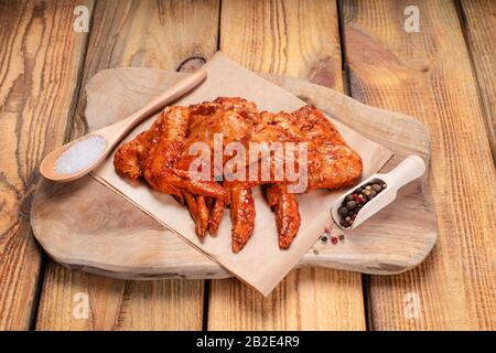 Chicken marinated meat.Raw pickled chicken wings on a blue plate on a wooden background. - Stock Photo