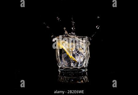 aqua water with lemon soda spills when ice is thrown with drops on a black backgroun