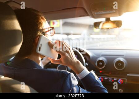 Man in blazer using and talking on smartphone while driving a car at sunset, looking carefully at the road, back view.