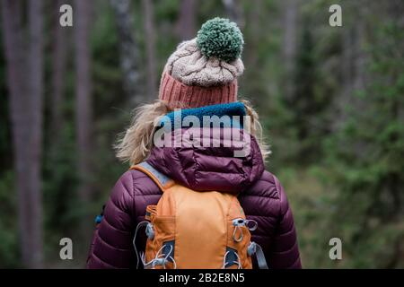 back of a woman standing in a forest in winter hiking with a backpack