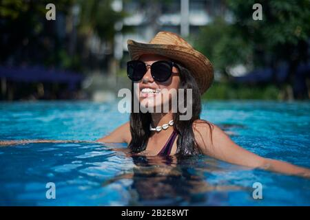 Stylish trendy young teen visco girl wearing a straw hat and necklace - Stock Photo