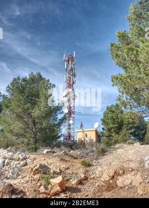 Remote mountain communications center with antennas on steel tower against a deep blue sky. - Stock Photo