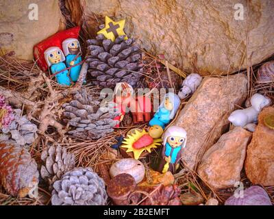 Childrens toy Nativity built in rocks. Presents from hikers walk around. Pintal Vermell pass, Mallorca island. Figures from a nativity scene or set wi - Stock Photo