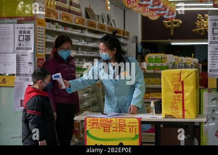 During the epidemic of coronavirus disease spreading to the world, medical store check-up body temperature for young boy. - Stock Photo