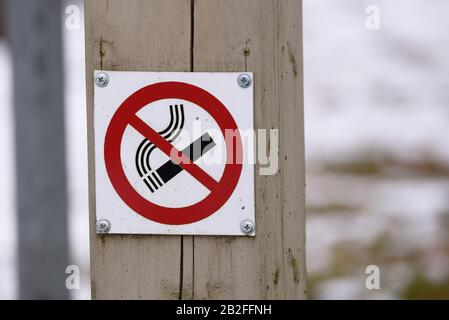 TALSI, LATVIA. 30h March 2018. No smoking sign on wooden pole at public place in city. - Stock Photo
