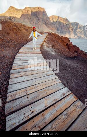 Woman walking on the picturesque wooden pathway through the rocky land with mountains on the background. Traveling on the north-west cape of Tenerife island, Spain