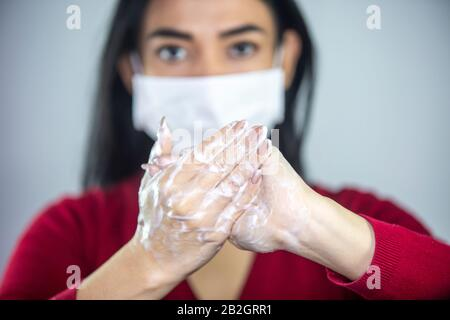 Woman wearing a face mask washing hands with soap to prevent spreading the bacterias and viruses. Corona virus concept.